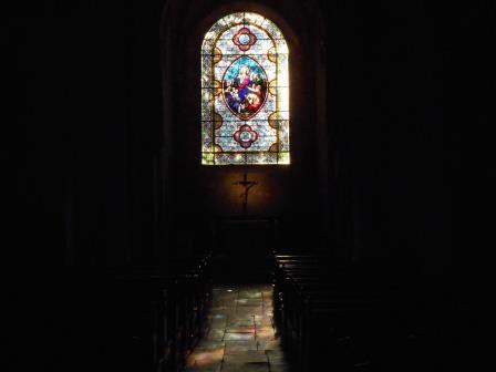 ステンドグラスの色彩が石床に映るカレナックのサン・ピエール教会